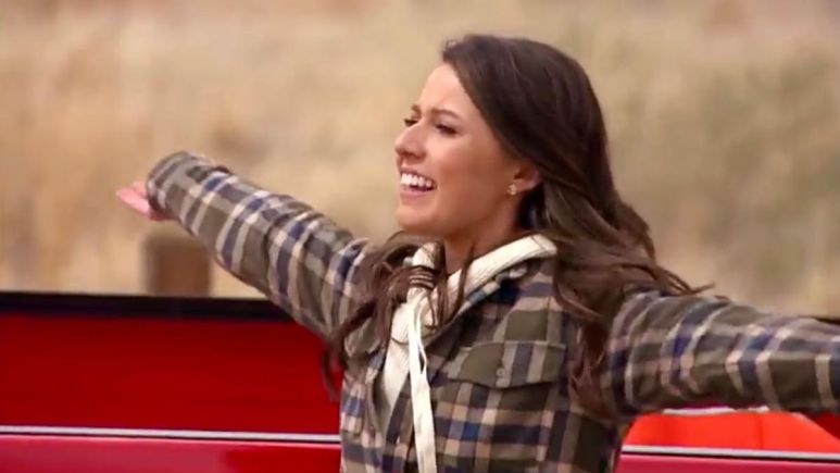Katie Thurston spreads her arms by a red truck