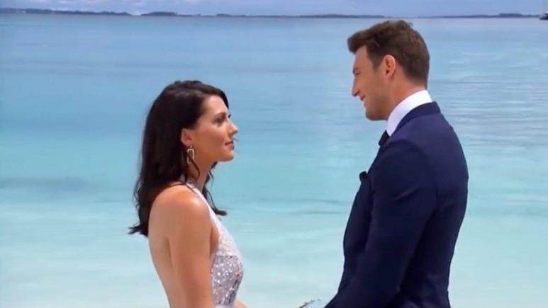 Becca and Blake wear formal attire by the ocean