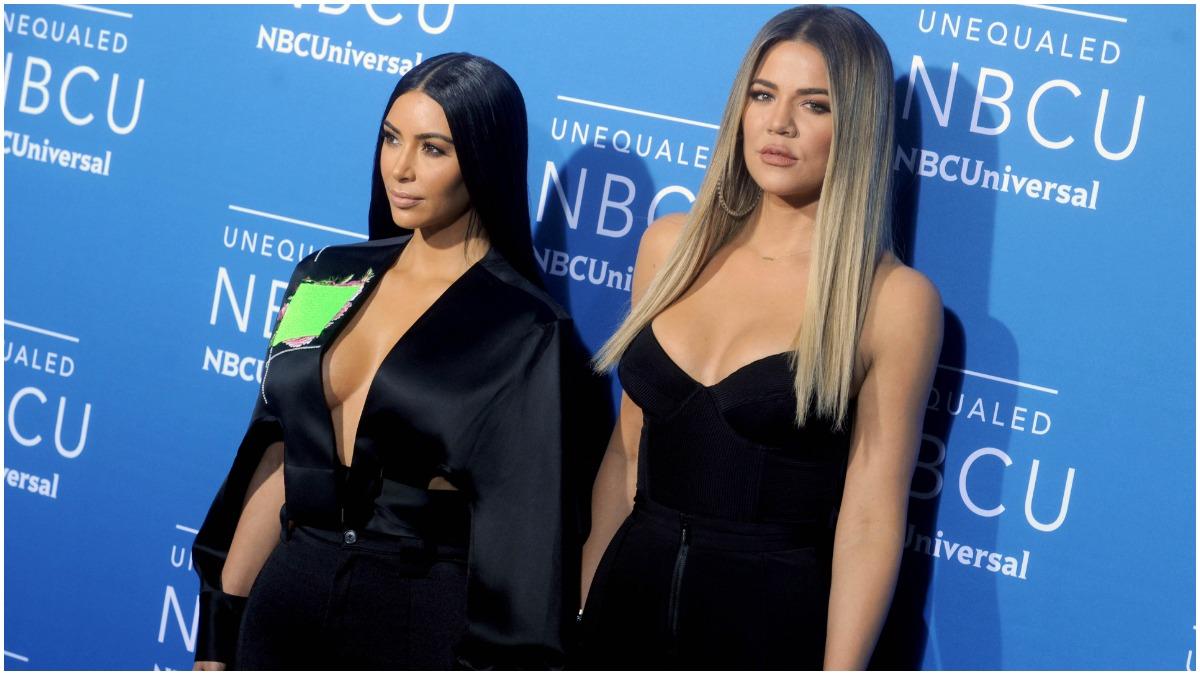 Kim Kardashian West and Khloé Kardashian wearing black outfits at a red carpet event.