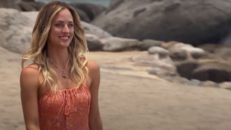 Kendall Long walking across the beach in a peach colored dress smiling