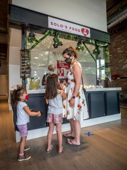 woman and children discuss what to order from Solo's Food counter