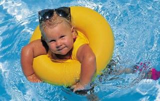 Toddler girl in rubber ring swimming