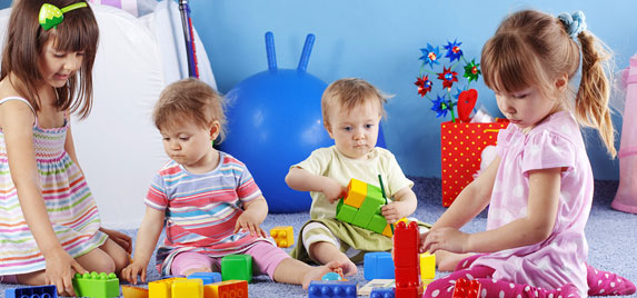 Toddlers playing with colorful building blocks