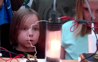 young girl looking at electric light experiment