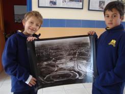 Nacho y Pancho sostienen una foto del Estadio Centenario, tomada en 1930