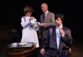 Mrs Hudson serves tea - Mrs. Hudson (Barbara Turner), Dr Watson (Paul Noga), and Sherlock Holmes (Matt Sims)