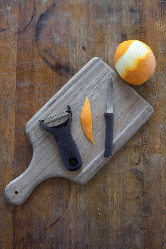 cutting board with an orange peel, orange, vegetable peeler, and a knife