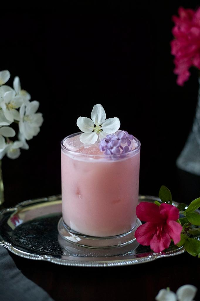 pink milky drink in a rocks glass on a silver tray with edible flowers
