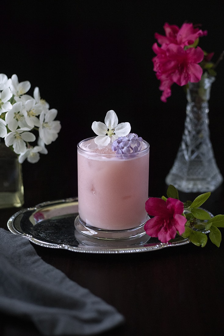 a rocks glass filled with pink milky beverage garnished with white and purple flowers