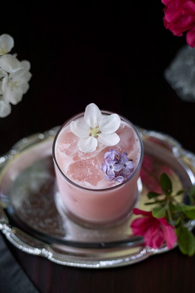 top down view of a pale pink milky drink garnished with an apple blossom and lilac flowers