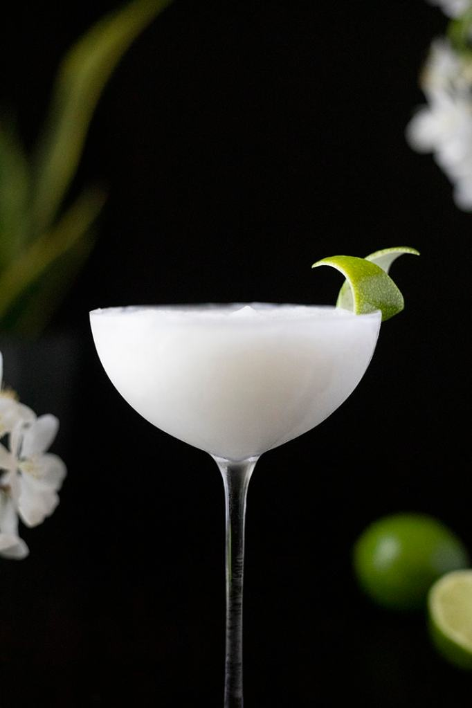 close up of a white frozen cocktail in a cocktail glass on a black background
