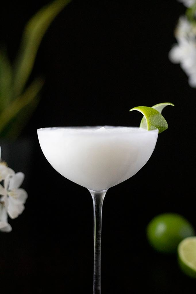 frozen white cocktail with lime peel garnish