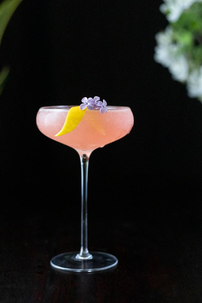 pale pink cocktail on a black background with small purple lilac flower garnish and a lemon twist