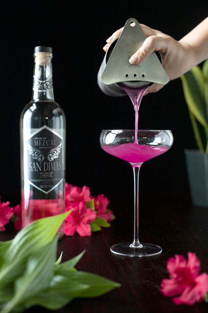 pouring a pink cocktail from the shaker into a tall coupe glass
