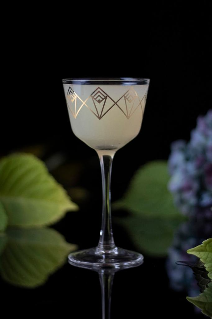 white cocktail in a gold embossed Nick and Nora glass