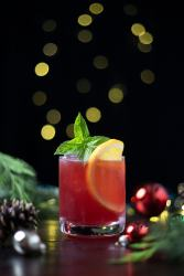 red drink garnished with basil and orange