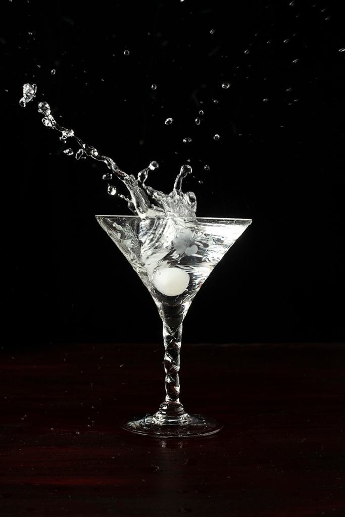 a cocktail onion splashing into a martini cocktail