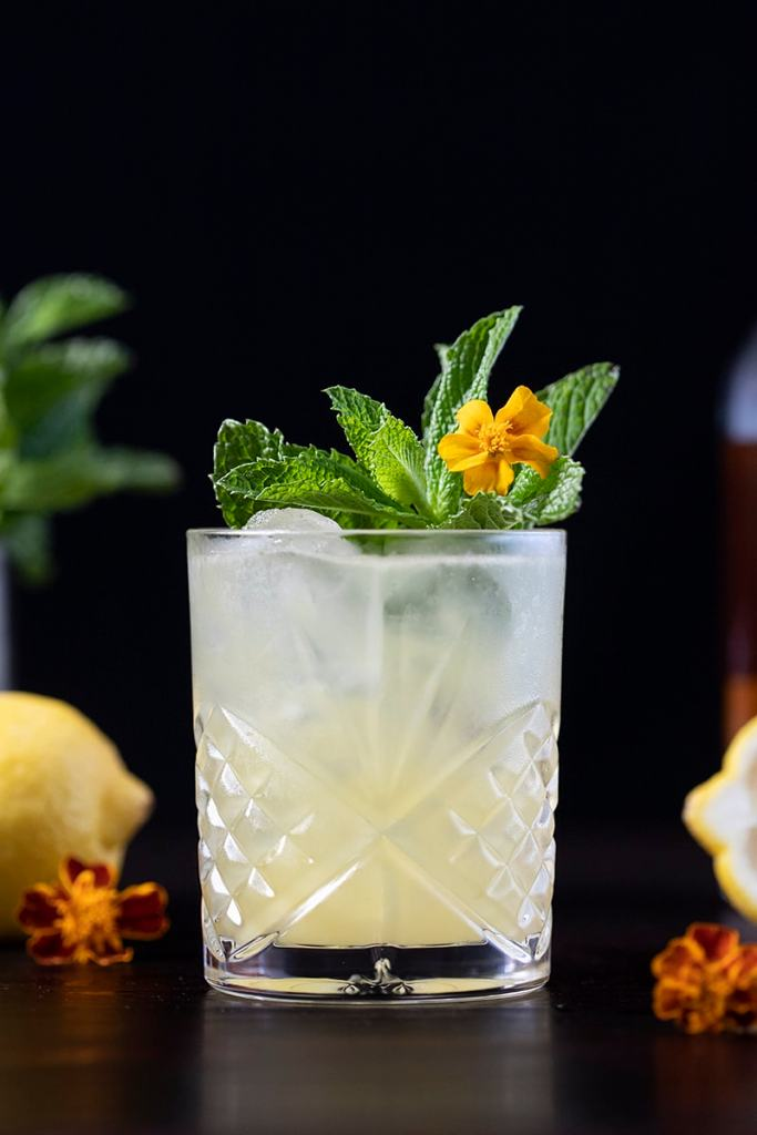 yellow cocktail with mint and a yellow flower