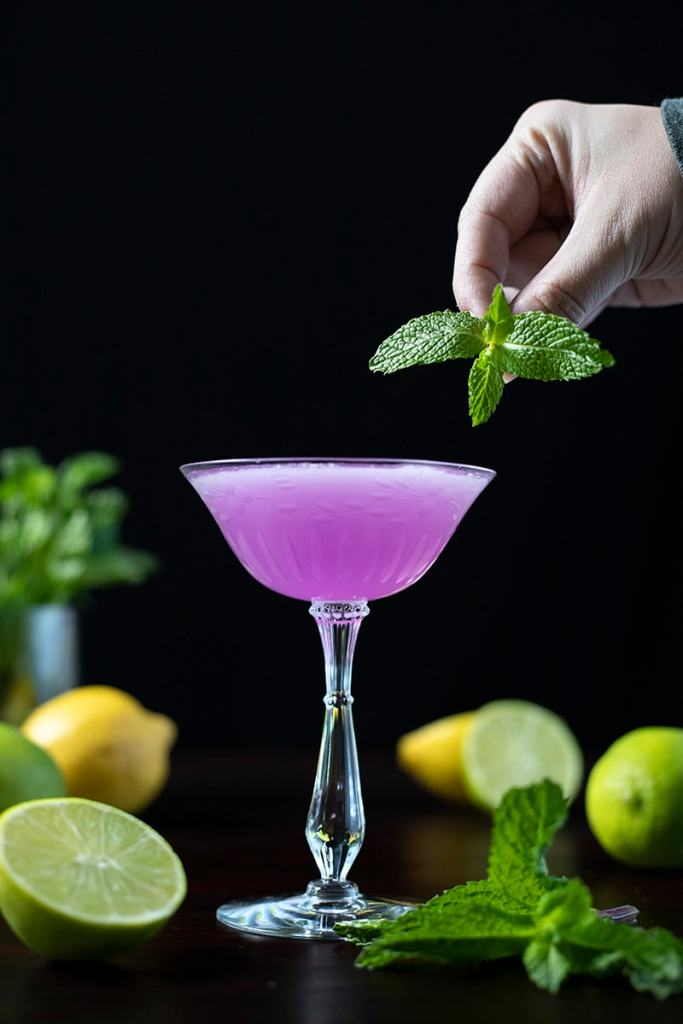 garnishing a cocktail with a sprig of mint