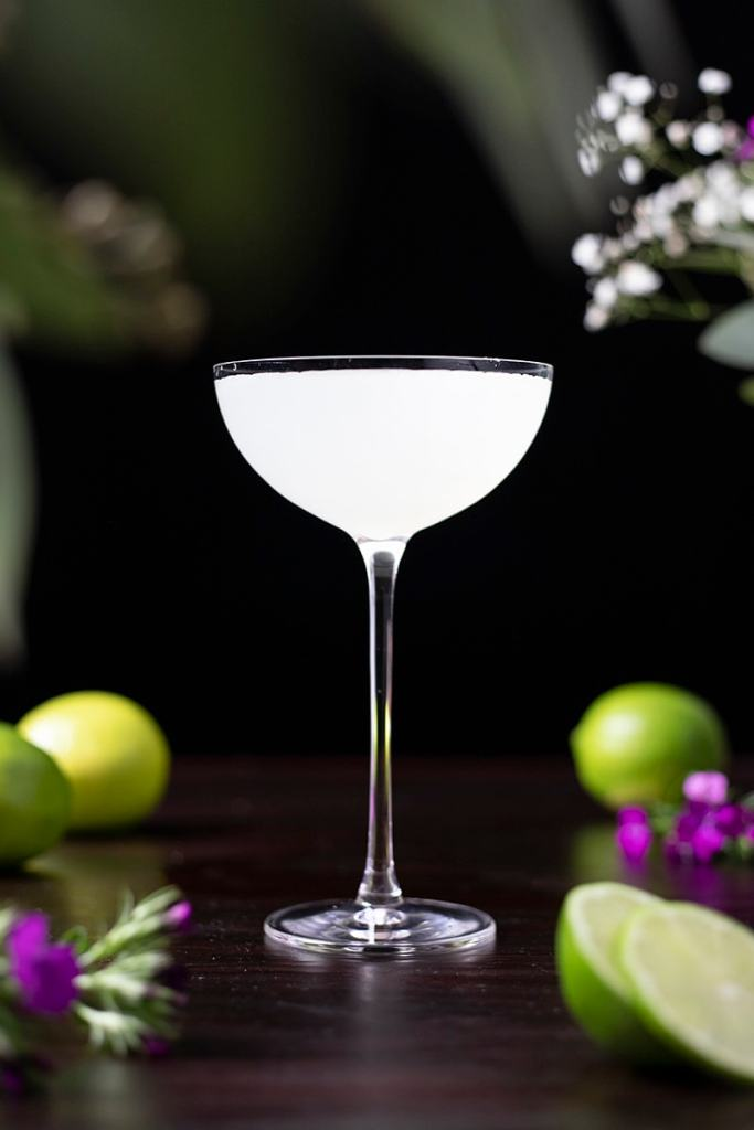 white cocktail on a table with limes