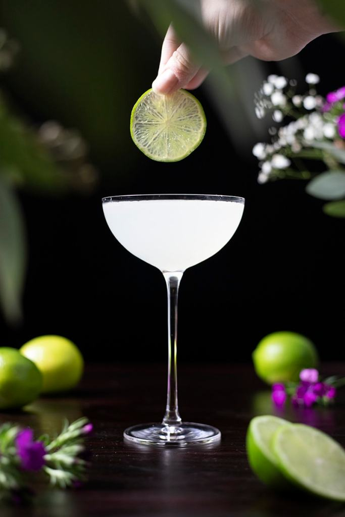 garnishing a cocktail with a lime wheel