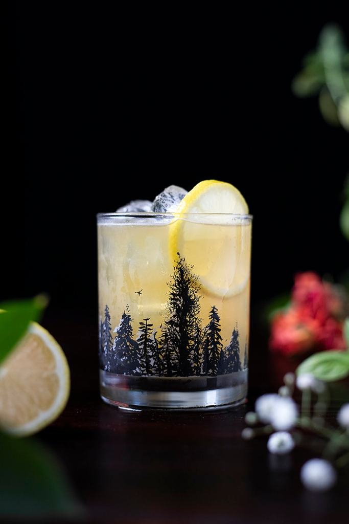 a yellow cocktail in a rocks glass with a forest outline on it
