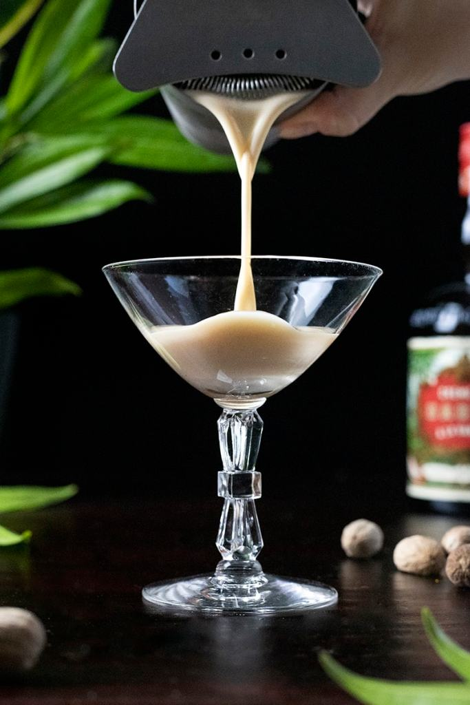 pouring a creamy cocktail into a coupe glass
