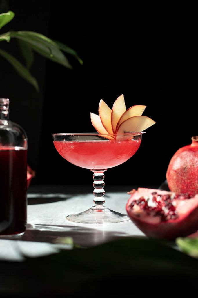 a red cocktail in a large vintage coupe glass garnished with an apple fan