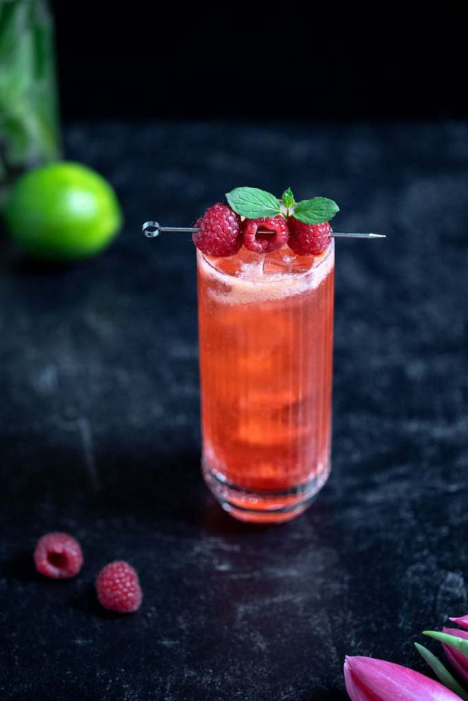 red drink in a tall glass with raspberries