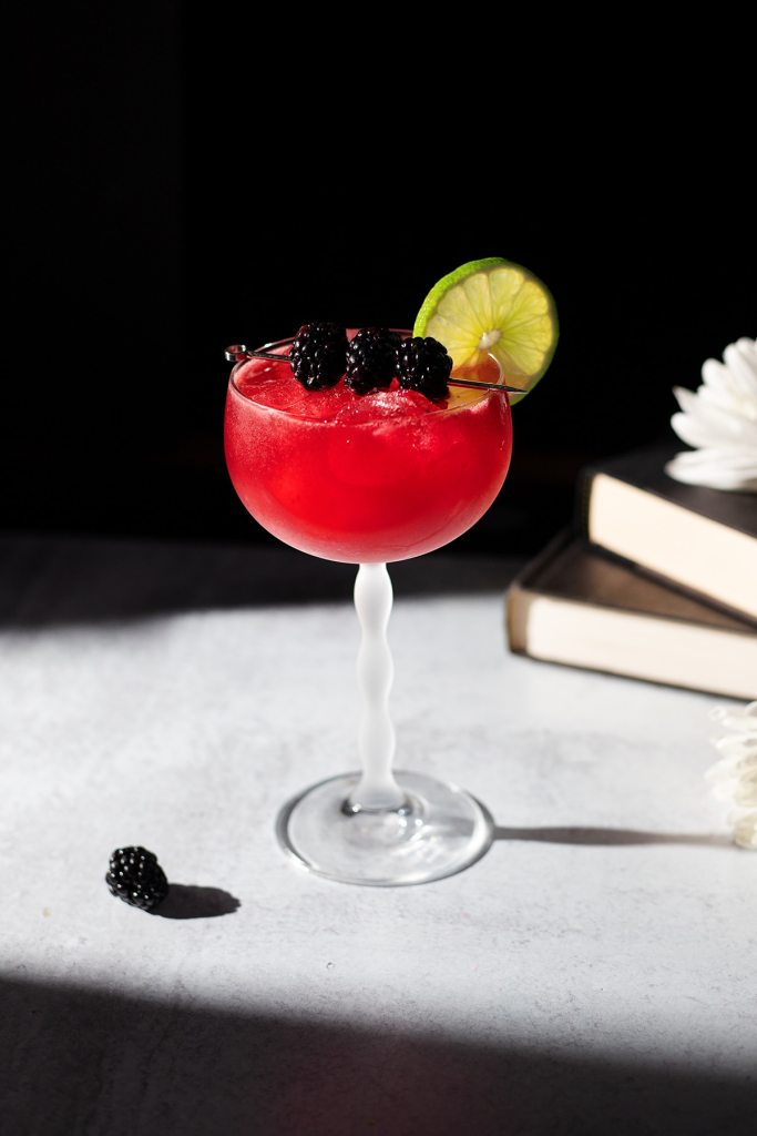 bright red cocktail in a stemmed glass garnished with blackberries and a lime wheel in the sun