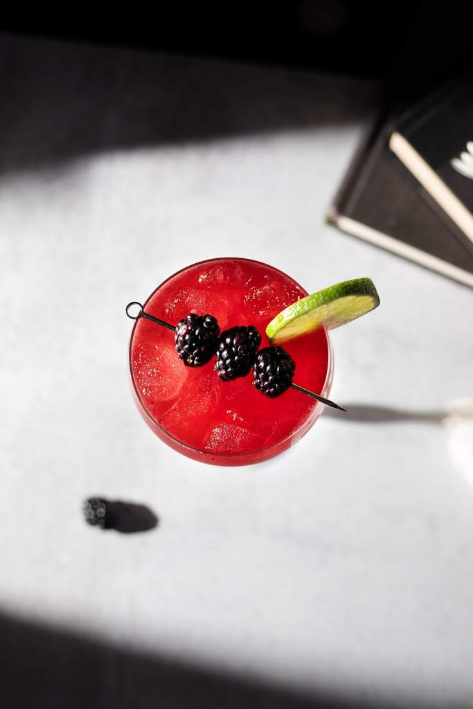 overhead view of a red drink garnished with fresh blackberries and lime