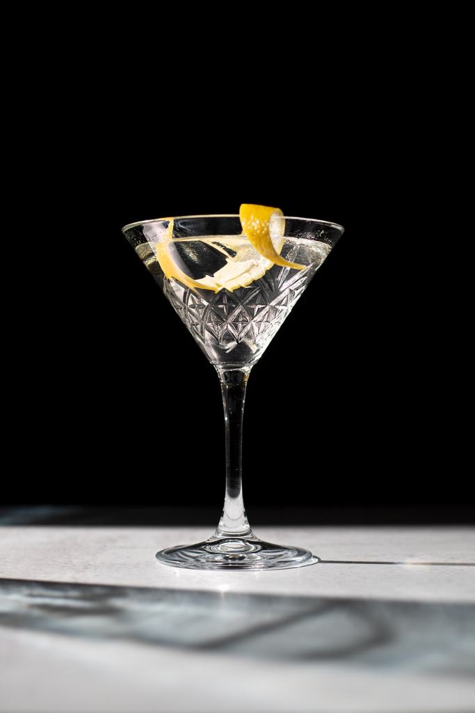 a martini with a lemon peel on a black background.