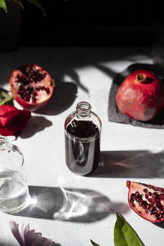 a bottle of dark red syrup surrounded by pomegrantes and flowers