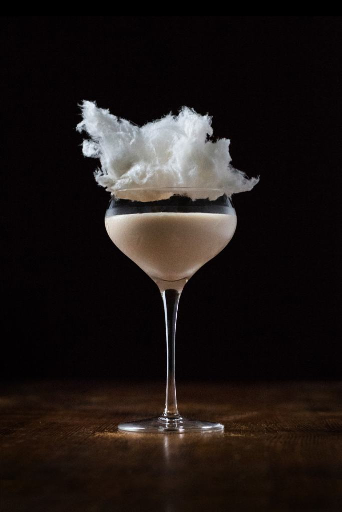 creamy cocktail in a coupe garnished with cotton candy.