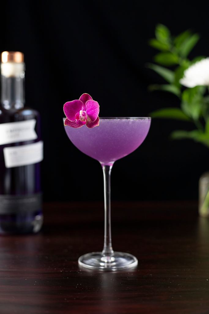 purple cocktail in a coupe glass next to Empress Gin bottle.