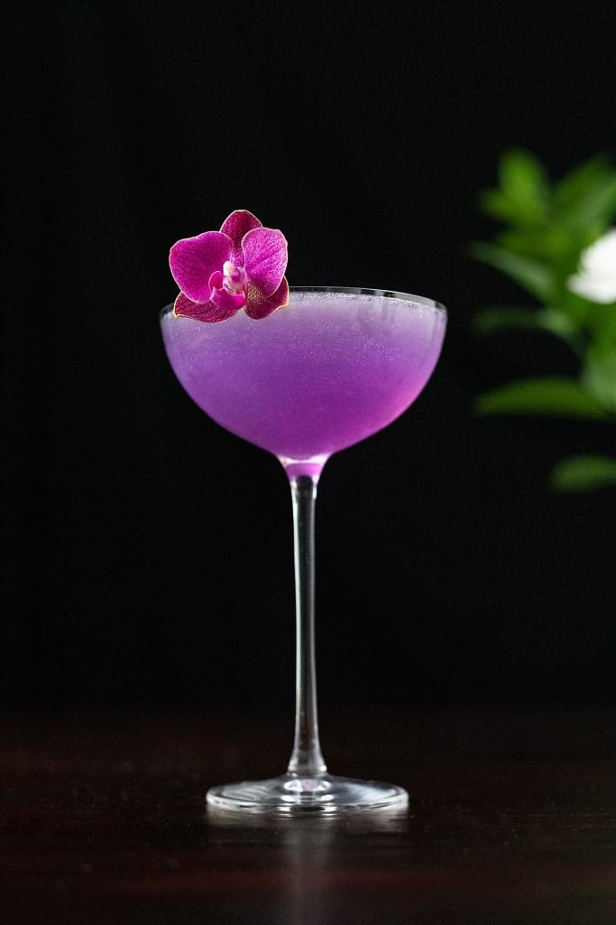 purple cocktail with a pink orchid in a coupe glass.