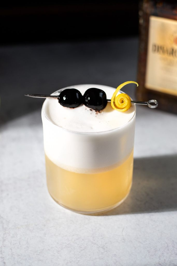 amaretto sour cocktail garnished with two cherries and a fancy lemon twist.