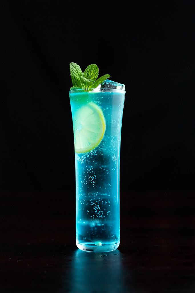 Blue cocktail garnished with mint.