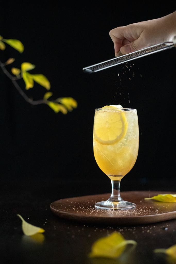 grating nutmeg over a glass of Fish House Punch