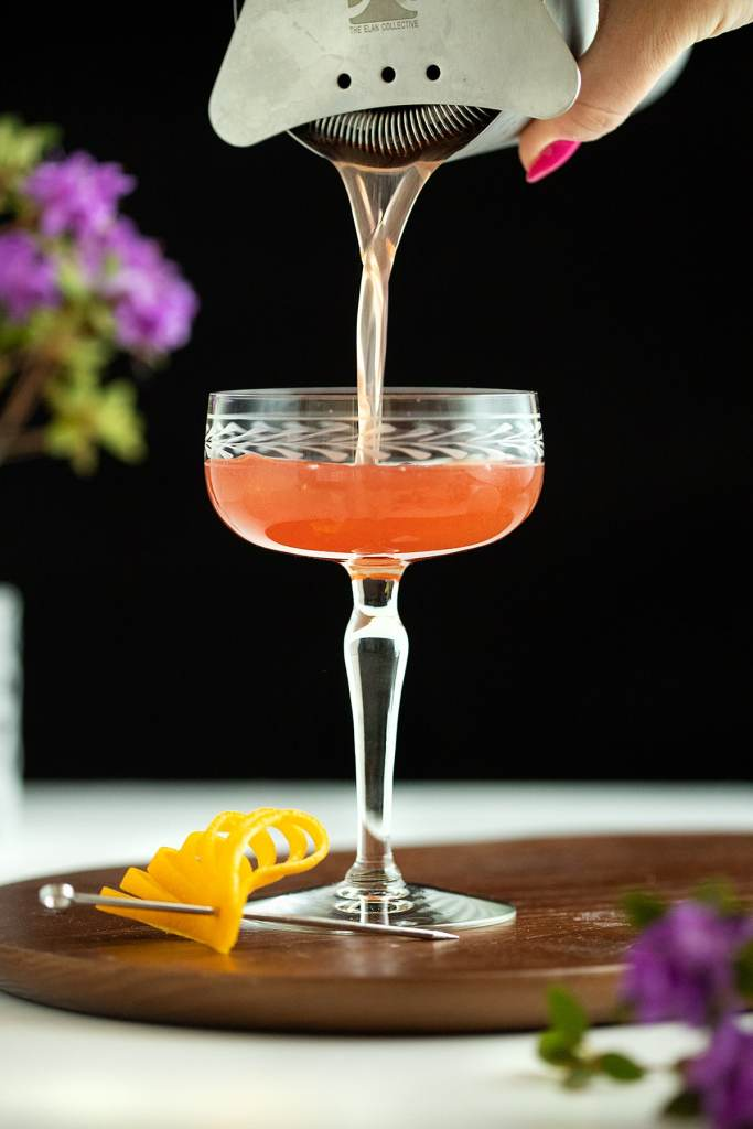 pouring a red cocktail into a vintage etched coupe glass.