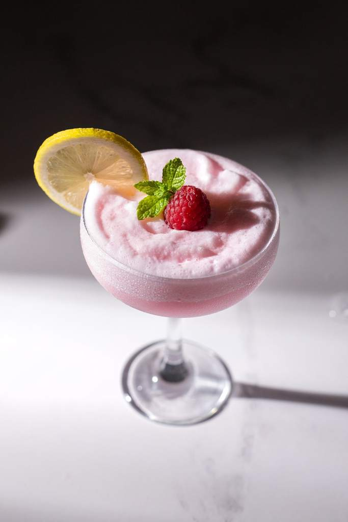 close up of a coupe glass filled with a pink foamy cocktail.