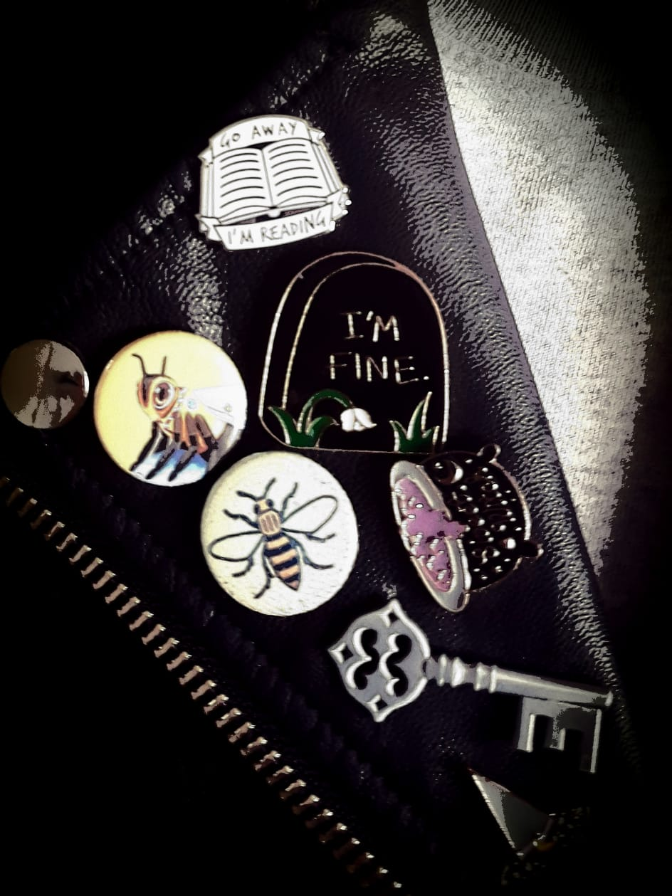 Collection of pin badges on leather jacket lapel, focusing on a'Manchester Bee'