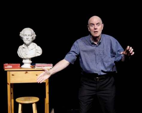 Performer Keir Cutler stands near a bust of Shakespeare