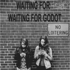 two women on cell phones, under a no loitering sign