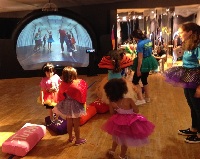 CMOM educators dance with visitors in Let's Dance!, while Elisa Monte Dance demonstrates a Soul Train on the Dance Portal screen, which is flanked by mirrors and a ballet barre.