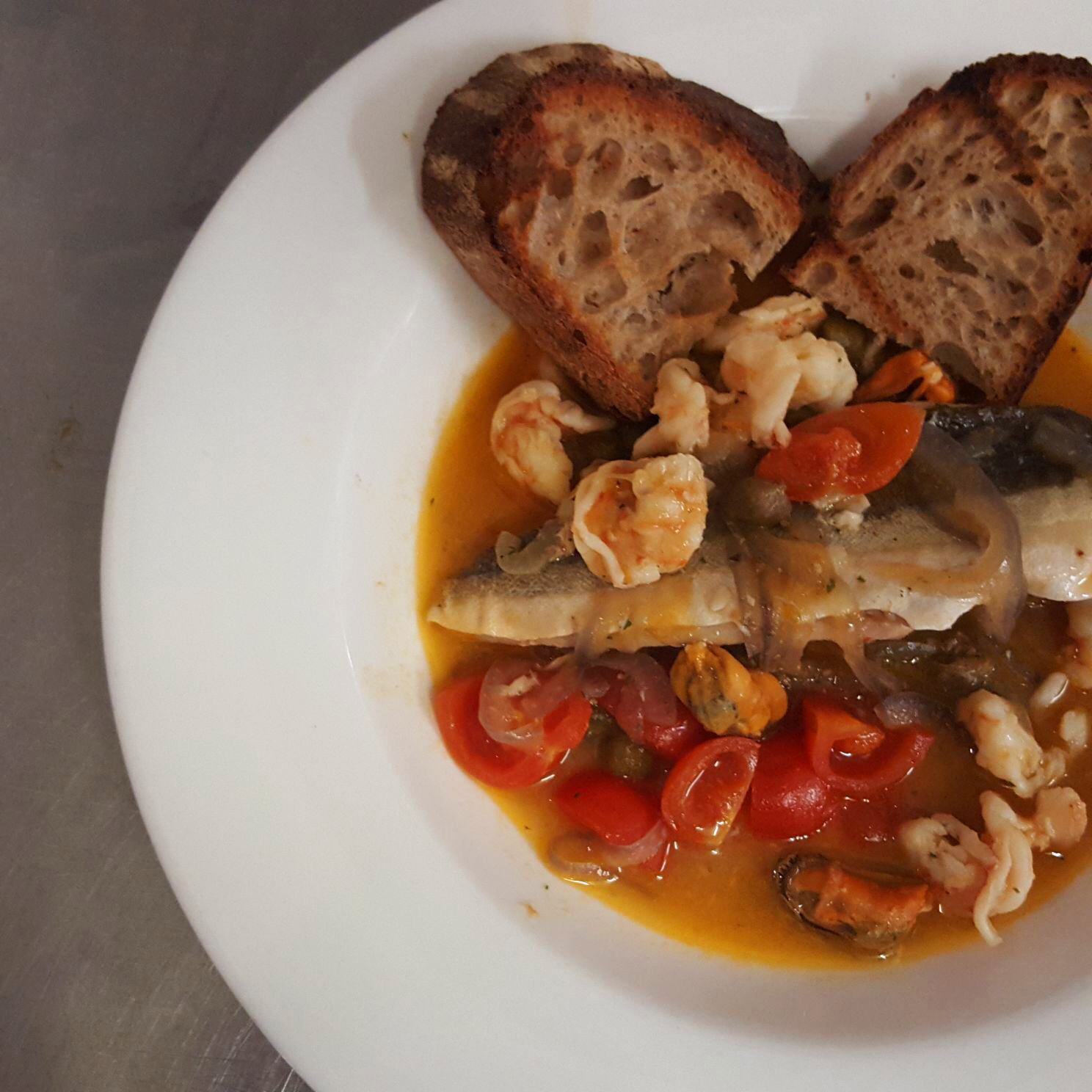 seafood stew. clams, mussels, prawns, gurnard, bisque and sourdough bread