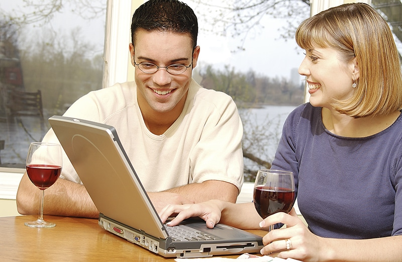 two people drinking red wine sitting a computer.