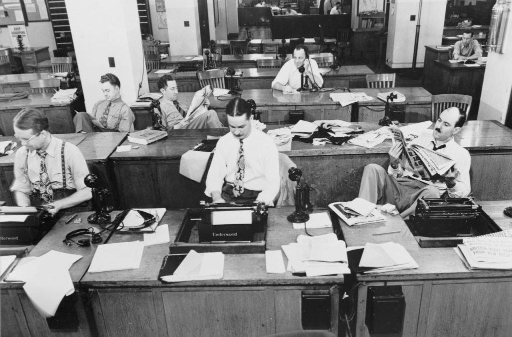 Guys sitting in a news room at typewriters. New york times