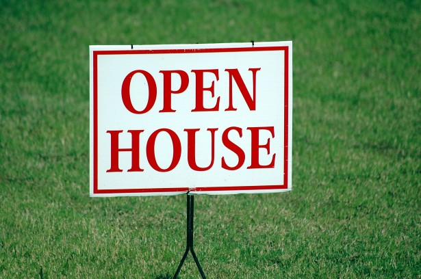 Green grass with open house sign stuck in the lawn