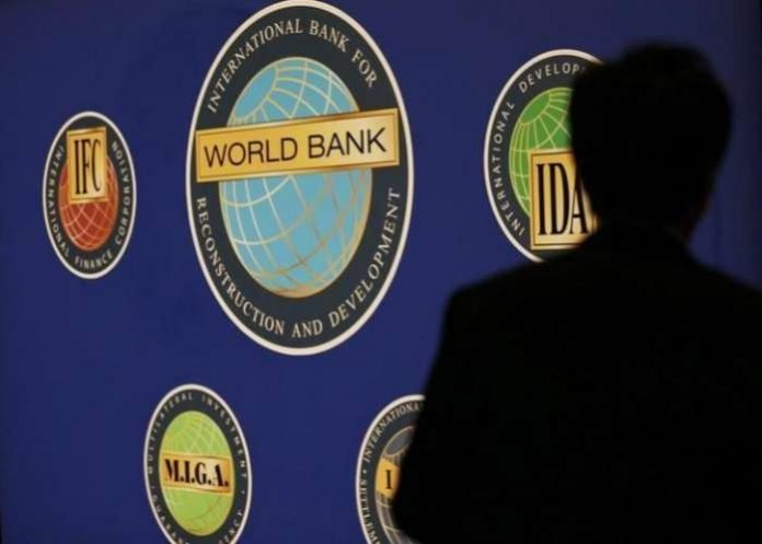 The silhouette of a man against the World Bank logo at the main venue of the annual meeting of the International Monetary Fund (IMF) and the World Bank in Tokyo.  REUTERS-Kim Kyung-Hoon